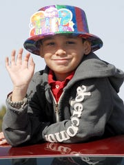 "Robin Zielinski/ Sun-News Ethan Garcia waves as he pops his head out of the top of a vehicle during the 2012 Leap Year parade in Anthony, N.M. Ethan was one of the youngest Leap Year babies to celebrate during the festivities that year: It was his ""second"" birthday."