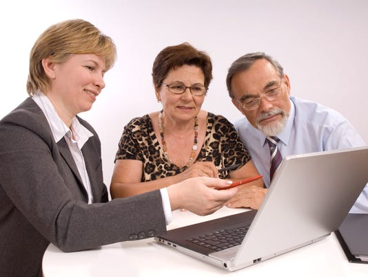 Woman pointing to laptop screen with elderly couple
