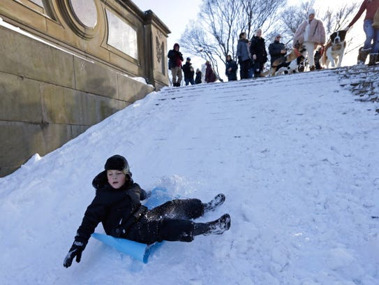 A young boy on a mat slides down the steps at Bethesda