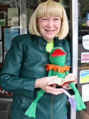 Jacqueline Schindele, with Salem Friends of Library, is promoting an upcoming favorite book sale. She holds a puppet named Guido.