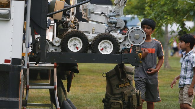 Brothers Jai Bajwa, 10, (left), and Udai, 8, of Newark, examine equipment on display by the New Castle County Police explosive ordnance disposal team, one of several displays during the Glasgow Park location of National Night Out on Tuesday.