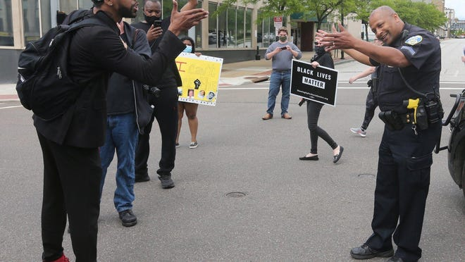 Akron police Sgt. Kevin Williams encourages protest leader Shawn Mansfield to move along as Mansfield stands in the middle of the Exchange Street and Broadway intersection shouting at officers on May 30.