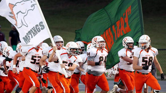 East Lincoln players run onto the field before their game against East Gaston Friday night.