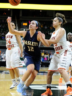 Haslett's Megan Mowid (12) tries to control the ball in the first half.  Haslett defeated Benton Harbor, 63-52, to advance to the Class B state final.