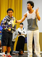 Performance artist Jamal Story, right, talks to Sakai