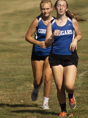 Mid-County's Abigail Lee, right, and Molly Warner compete in the triangular cross country meet on Thursday, Aug. 27, at Galva Park.