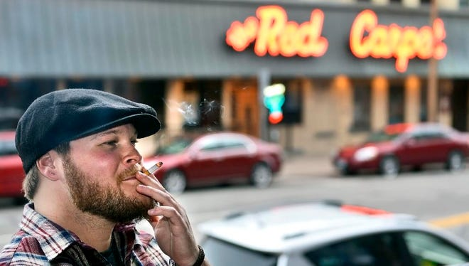 Jon Schulte, St. Joseph, enjoys a cigarette with friends Wednesday, Sept. 24 on the veranda of the Veranda Lounge in the Pioneer Place on Fifth building in downtown St. Cloud.