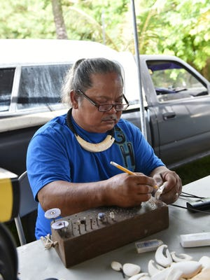 Guahan Heritage Carving's George Francisco carves a design out of tabo at Inarajan's Sunday Market Street Festival on Aug. 23.