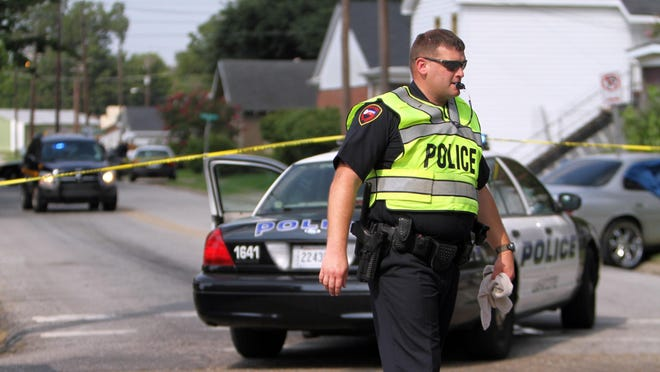 In this file photo, police investigate a shooting that resulted in the death of a man and injury to a woman on University Avenue.