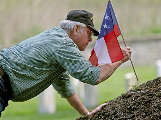 R. Hugh Simmons, with the Fort Delaware Society, prepares to put memorial flags around a monument with the names of Confederate soldiers in Finn's Point National Cemetery in Pennsville, N.J. The soldiers died when they were at Fort Delaware on Pea Patch Island during the Civil War.