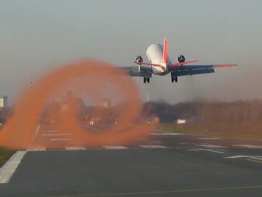 A plane creates wingtip vortices as it takes off.