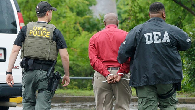 An unidentified man, center, is escorted from a medical clinic in Little Rock, Ark., by Drug Enforcement Administration officers Wednesday, May 20, 2015. Early-morning raids in Arkansas, Alabama, Louisiana and Mississippi were the final stage of an operation launched last summer by the DEA's drug diversion unit, a senior DEA official said, speaking on condition of anonymity.