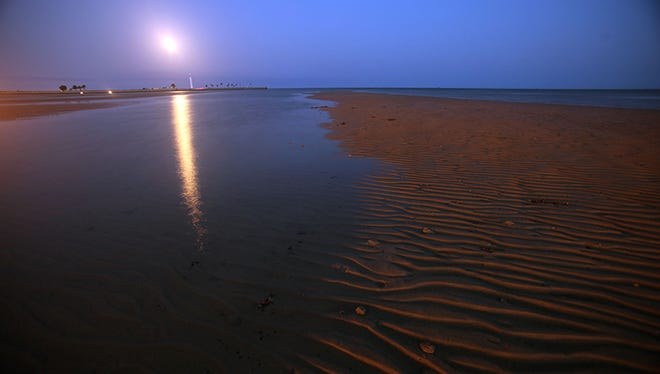 The full moon rises over Biloxi's beach and lighthouse April 17, 2011 in Biloxi, Mississippi. Biloxi's beaches continue to be impacted by tar balls and weathered oil from the BP oil spill.