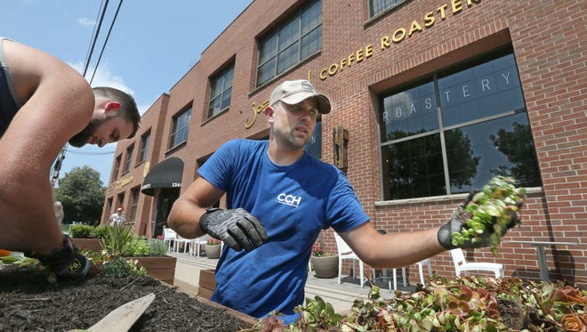 Chris Horn, right, owner operator of CCH Lawn & Landscaping, Greece, and employee Dave Bianchi, left, fill one of twelve planters with greenery as they help install a parklet outside Joe Bean Coffee Roasters on University Avenue in Rochester Thursday, Aug. 3, 2017.  The parklet is the first of its kind in Rochester.