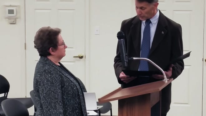 Rep. Ronald Gray, R-Ocean View, reads a proclamation honoring the late Thomas Sheeran on behalf of the state House of Representatives to Sheeran's widowed wife, Patricia.