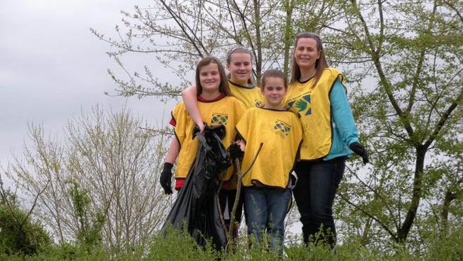 Teena Smith, far right,  and her three daughters, Haley, Aleesia and Kaitlyn, bag broken limbs and garbage along the Heritage Rail Trail. Smith and her daughters are members of the West York Ward of The Church of Jesus Christ of Latter-day Saints.