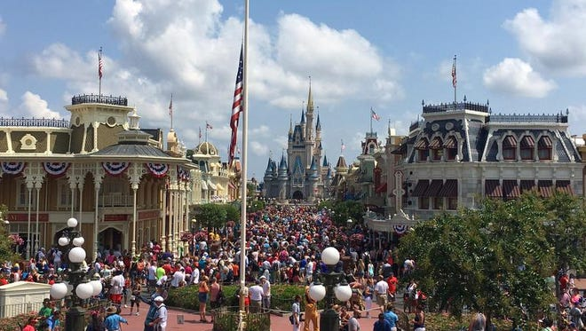 The flag is lowered to half-staff on Monday, June 13, 2016, in Walt Disney World's Magic Kingdom in honor of the victims who died in the Pulse nightclub shooting in Orlando (Dewayne Bevil/Orlando Sentinel via AP)  MAGS OUT; NO SALES; MANDATORY CREDIT