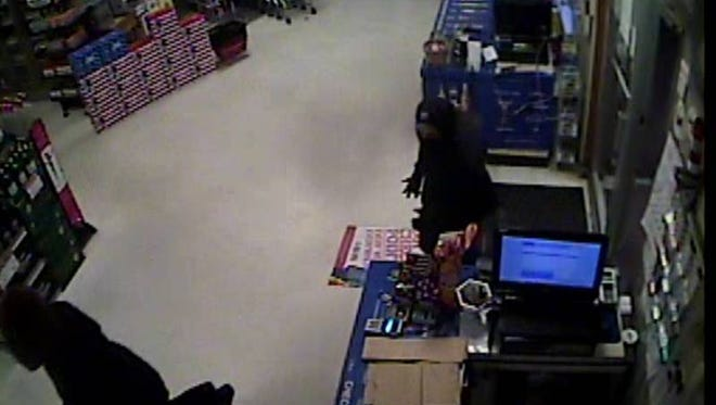 In this still taken from security camera footage, two robbers enter Hickman's Package Store in Ocean View and approach the cashier. The cashier was not injured in the incident.