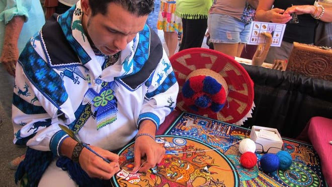 In this July 11, 2015, file photo, Rafael Cilau Valadez, of Mexico, works on a Wixarika yarn painting during the 12th annual International Folk Art Market in Santa Fe, N.M. Now in its 13th year, the 2016 International Folk Art Market will feature artists from more than 60 different countries, and organizers say this year marks an opportunity to celebrate differences despite ongoing strife around the globe. (AP Photo/Susan Montoya Bryan, File)