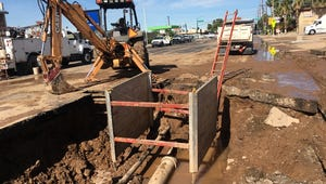 Crews with the City of Phoenix Water Services Department work to fix a water main break on Camelback Road in Phoenix.