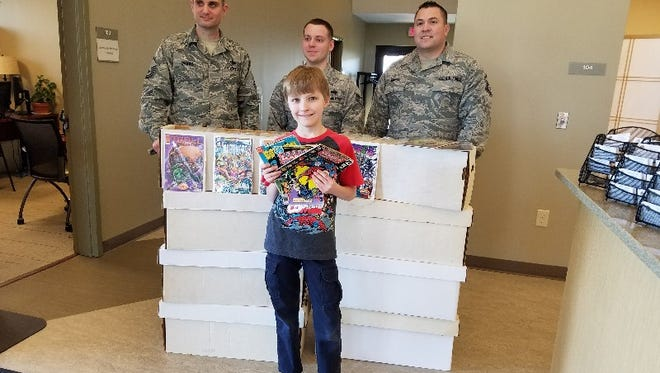 Carl Scheckel, 10, stands with the boxes of comics he has donated to the troops at the Joint Base McGuire-Dix-Lakehurst. Behind him are, from left, Master Sgt. Robert Vaughan, Staff Sgt. Scott Thomas, and Sgt. Dominick Griego.