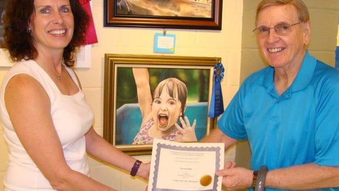 A Participant of the Hunterdon County Senior Art Exhibition shows off his work
