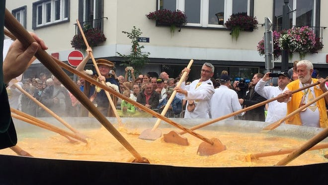 Cooks and volunteers stir eggs on an oversize pan at the 22nd Giant Omelet event in Malmedy, Belgium, Tuesday, Aug. 15, 2017.