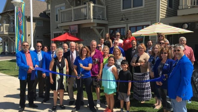 Mayor Mike Vandersteen and Chamber Executive Director Betsy Alles cut the ribbon for New Life with owner Kim Boettcher and her partner, Dan Wilson. They are joined by their team, friends and Chamber ambassadors.