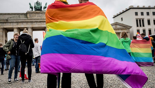 Men with rainbow flags stand in front of the Brandenburg Gate at an event organized by the Social Democrats to celebrate the legalization of same-sex marriage in Berlin, Germany, on June 30, 2017.