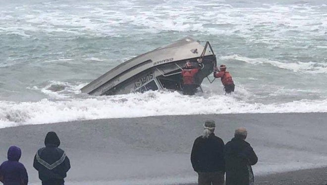 Two Coast Guardsmen from Station Chetco River work to rescue a man from the cabin of an overturned U.S. Army Corps of Engineers survey vessel resting on the beach in Brookings, Ore., April 25, 2018.The man was successfully rescued after being trapped in the overturned boat for more than 40 minutes.U.S. Coast Guard photo courtesy Station Chetco River.