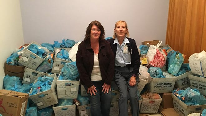 Brenda Heckman (left) from the Windsor Food Pantry poses next to Windsor Letter Carrier Food Drive coordinator Donna Schurger with the donations from 2016.