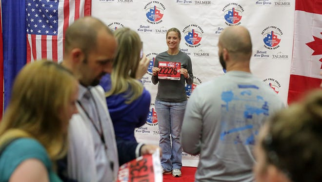 Jessica Wolf, 32, of Livonia gets her photo taken by her friend, Catherine Kelley, who motivated her to run the international half marathon at the Detroit Free Press/Talmer Bank Marathon Health & Fitness Expo at Cobo Center on Friday.