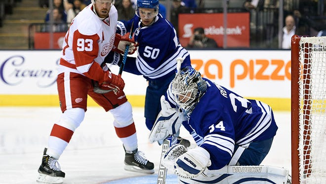 Red Wings forward Justin Abdelkader, left, scores against Maple Leafs goalie James Reimer during the third period of the Wings' 4-1 win Friday in Toronto.