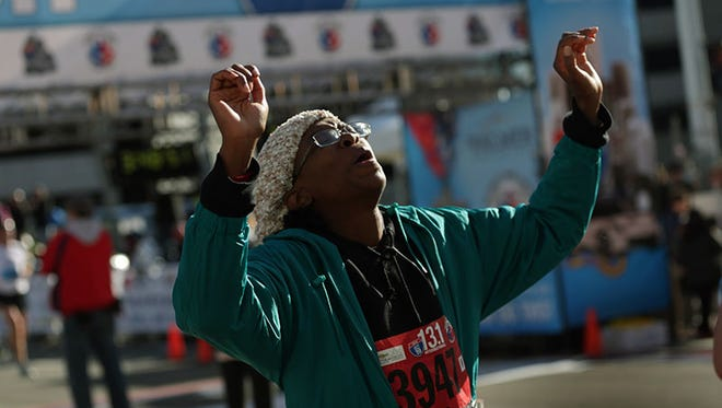 Leona Burns of Oak Park reacts after finishing her half marathon during the 37th Annual Detroit Free Press/Talmer Bank Marathon on Sunday.