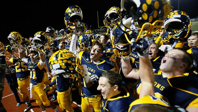 South Lyon players lead a cheer to their fans celebrating their 17-7 win over Canton on Friday.