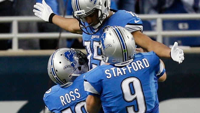 Lions Jeremy Ross and Matthew Stafford celebrate with Golden Tate after his long touchdown catch-and-run in Sunday's win over the Saints.