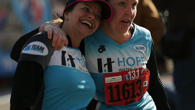 Susan Adams of Troy, left and Deanna Nowakowski of Troy react after finishing the half marathon during the 37th Annual Detroit Free Press/Talmer Bank Marathon on Sunday.