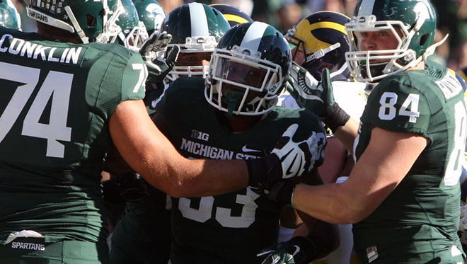 MSU RB Jeremy Langford celebrates his touchdown against Michigan on Saturday in East Lansing.