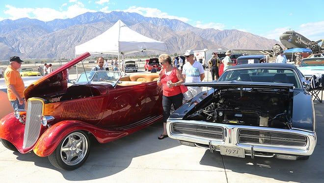 People admire two wildly different hot rods on display at the Palm Springs Air Museum's annual chili cook off and car rally Saturday, October 25, 2014.