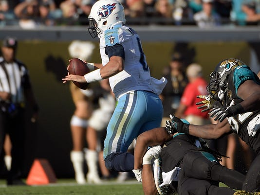 Tennessee Titans quarterback Marcus Mariota, left, is injured as he is stopped by the Jacksonville Jaguars defense during the second half of an NFL football game, Saturday, Dec. 24, 2016, in Jacksonville, Fla. Mariota left the field in a cart after his injury. (AP Photo/Phelan M. Ebenhack)