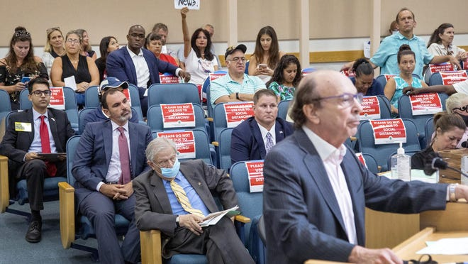 Irv Slosberg, former state House member and candidate for state Senate, speaks Tuesday in favor of masks at the Palm Beach County Commission meeting.  Maskless opponents await their turn at the lecturn behind Slosberg.