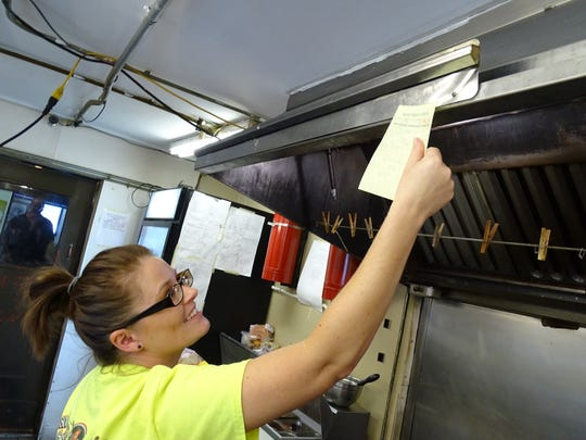 Maggie Schifer, a server at the Bucyrus Diner, places an order ticket in the kitchen Thursday.