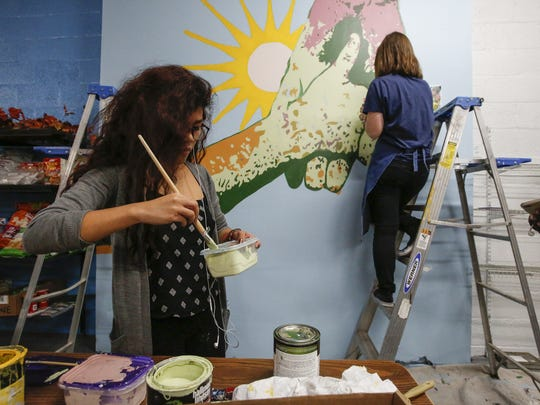 Silver Lake College students Brianna Thetphasone, left, and Kaye Solander work on a mural of two hands inspired by an image found on banana boxes used at Peter's Pantry Nov. 7 in Manitowoc. This mural is one of three students painted in an effort to brighten up the interior of the food pantry.