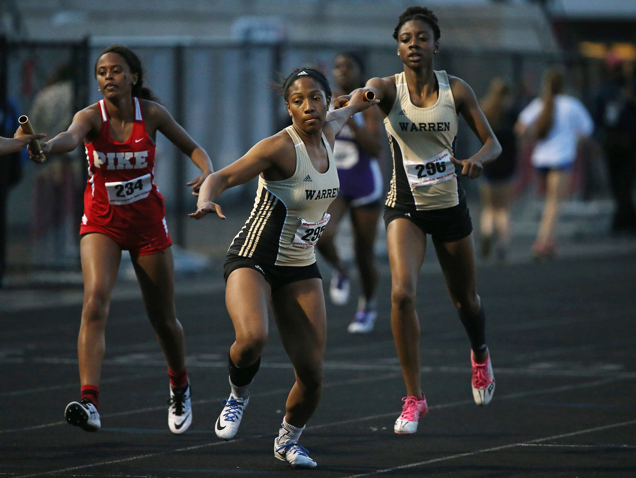 Center, Warren Central junior Ashley Baker takes the relay stick, right, sophomore Kennedy Batts, during a Marion County girls track meet at North Central High School, Tuesday, May 10, 2016. Warren Central won the 4 x 400 meter relay.