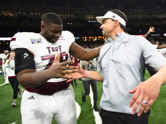 Troy offensive lineman Kirk Kelley (78) celebrates with Troy head coach Neal Brown after the New Orleans Bowl between Troy and North Texas at Mercedes-Benz Superdome in New Orleans, La., on Saturday, Dec. 16, 2017. Troy defeated North Texas 50-30.