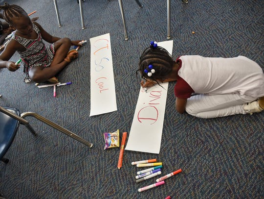 Children create drawings for an art project Friday,