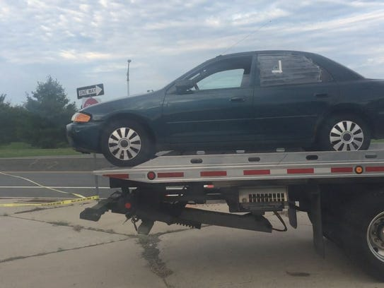 A car is towed away from the scene of a fatal shooting
