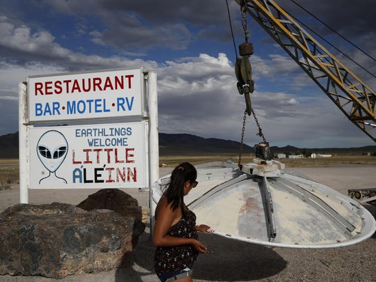 Grace Capati looks at a UFO display outside of the Little A'Le'Inn, in Rachel, Nev., the closest town to Area 51.