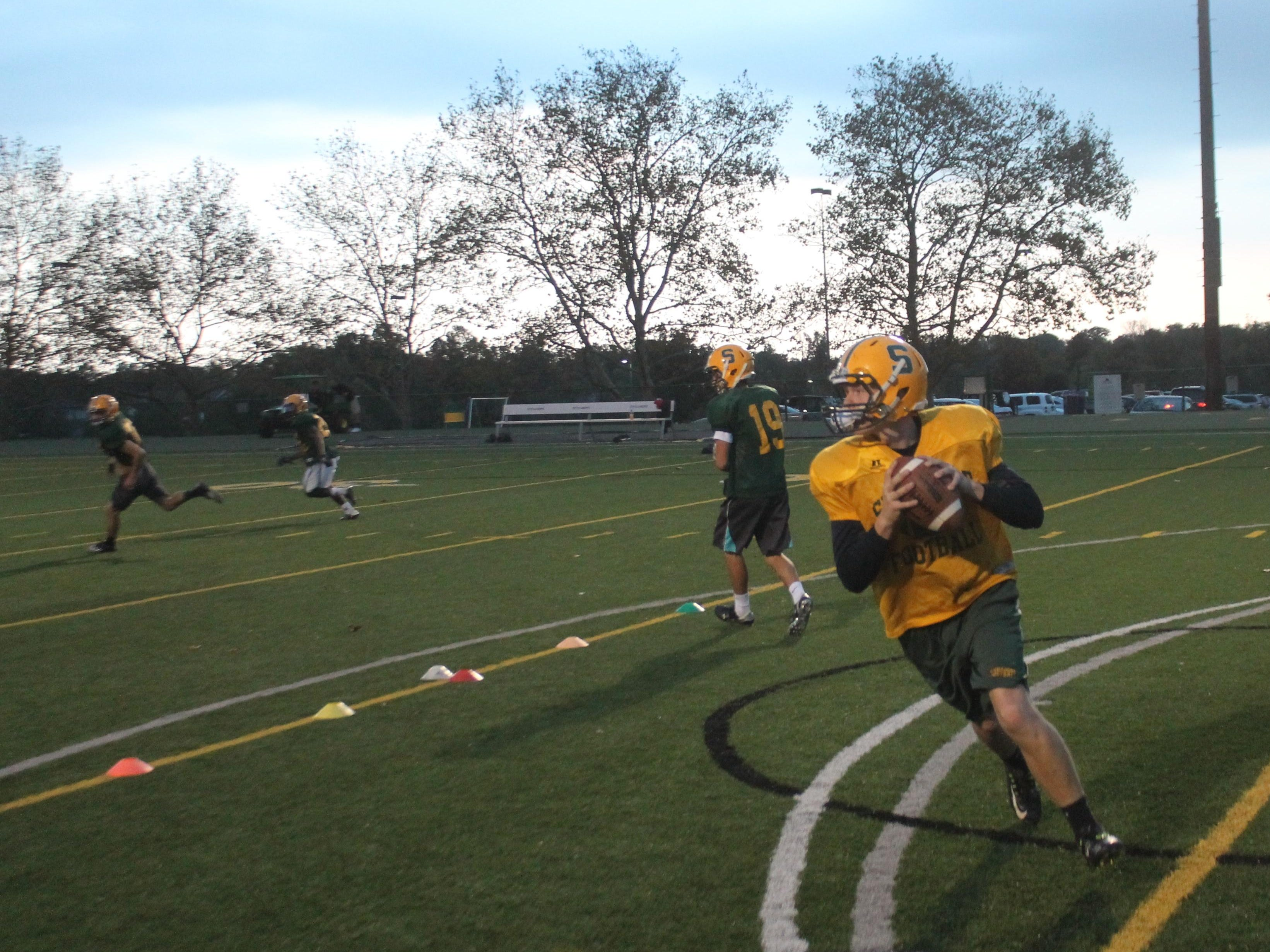 Junior Jake Borman rolls out in practice for the Aviators as the sun sets on Sycamore High.