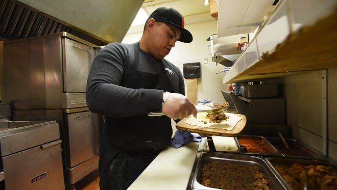 Raul Reyes prepares a sopapilla at El Parian in South Zanesville. The Mexican restaurant features nearly 200 items on its menu, with the sopapilla being one of the most popular.